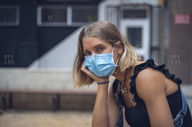 Beautiful girl, with a face mask looks towards the camera, with tired and disgusted face.