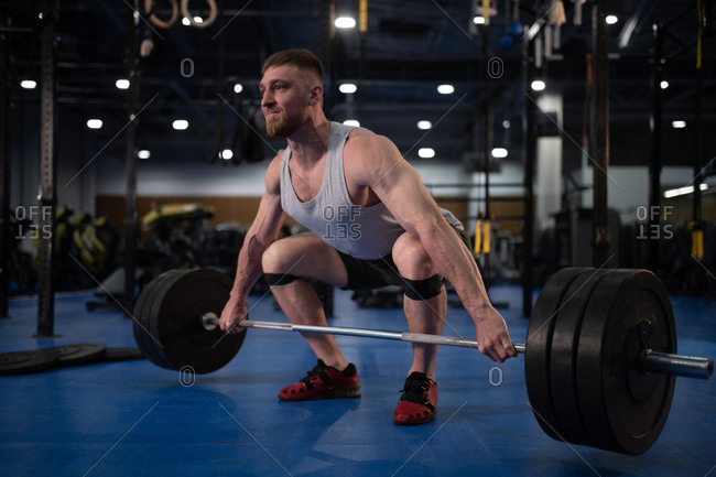 Strained sportsman deadlifting barbell in gym