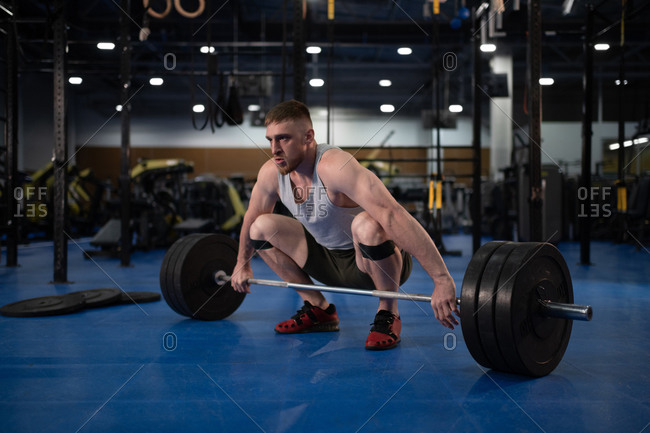 Male athlete squatting and lifting barbell
