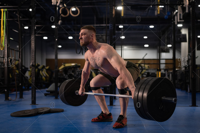 Masculine weightlifter squatting with barbell