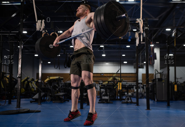 Bearded weightlifter deadlifting barbell on tiptoes