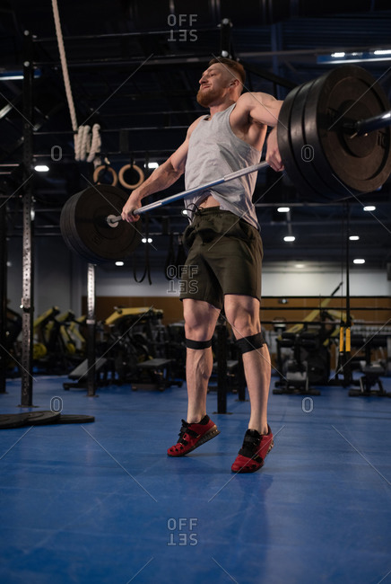 Powerful athlete lifting weight with effort