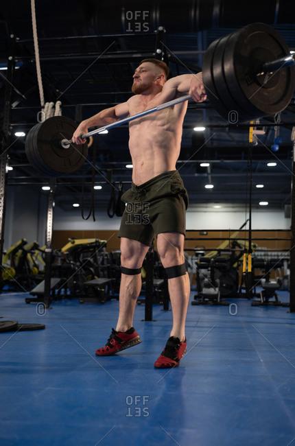 Man lifting barbell during intense workout
