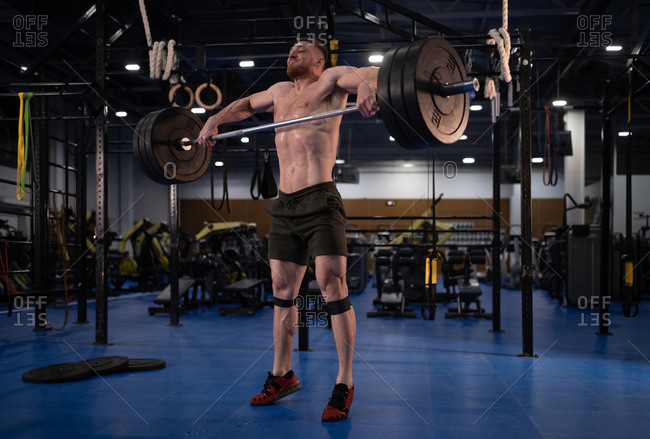 Sweaty weightlifter lifting barbell with effort