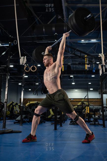 Brutal sportsman with barbell over head