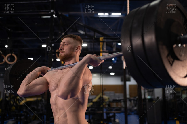 Powerful athlete lifting barbell in gym