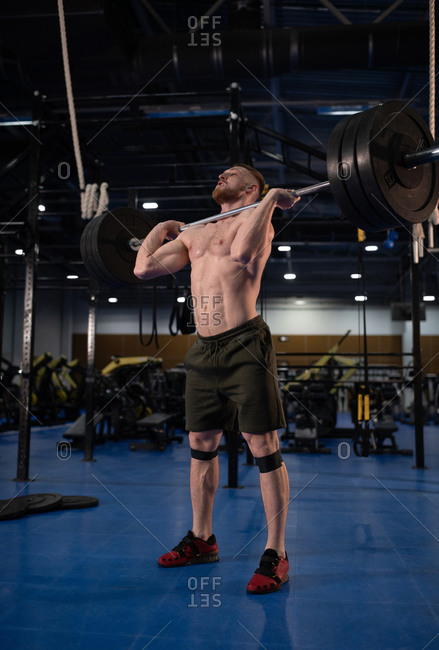 Male athlete with barbell training in gym