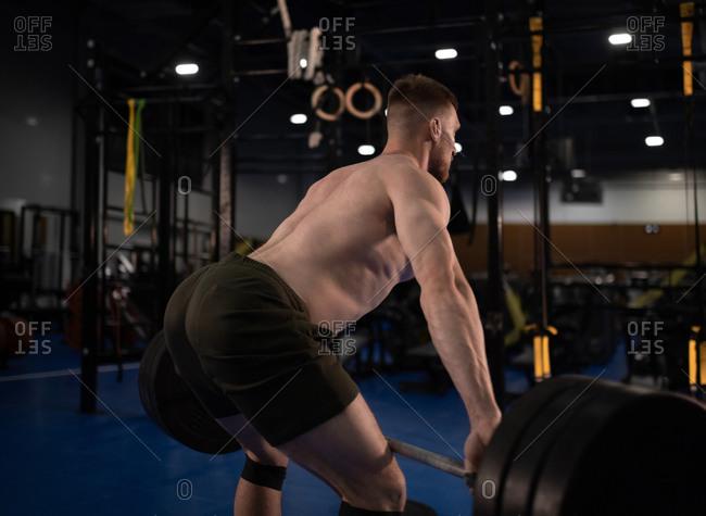 Sportsman in shorts deadlifting barbell