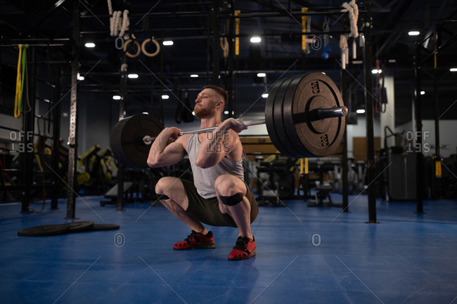 Sportsman ready to push barbell from squat