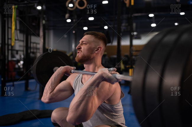 Aggressive weightlifter doing front squat