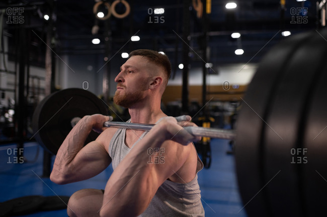 Focused athlete squatting with barbell