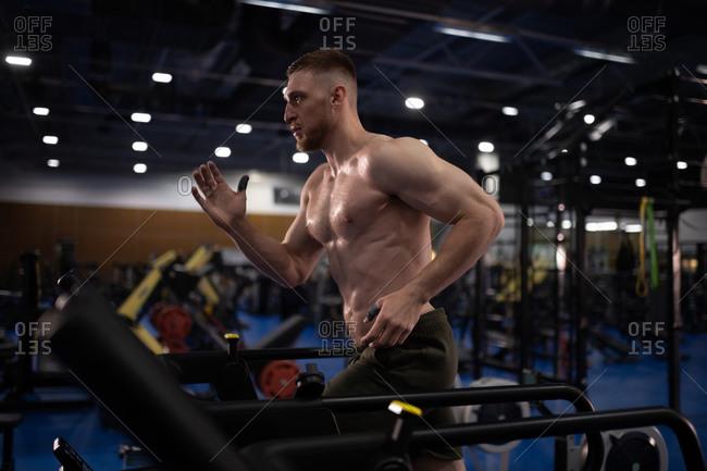 Powerful athlete running on treadmill