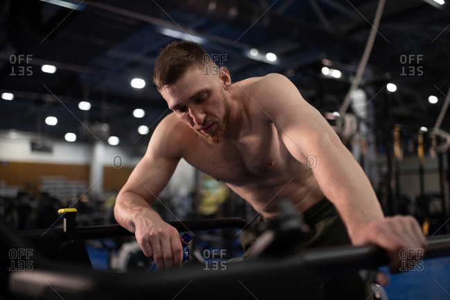 Exhausted sportsman resting on treadmill