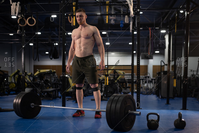 Aggressive sportsman ready to exercise with barbell