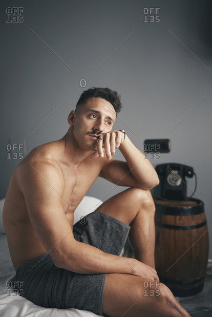 Portrait of a young boy with a boring moustache in his room