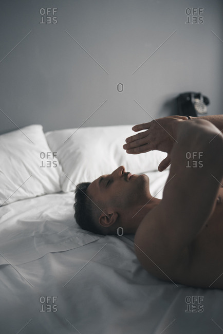 Portrait of a boy with a moustache praying in bed