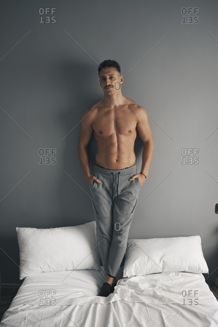 Portrait of a boy with a moustache standing on the bed