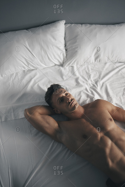 Portrait of a naked boy lying in bed resting