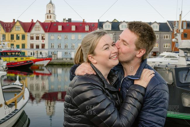 Loving couple kissing on urban embankment