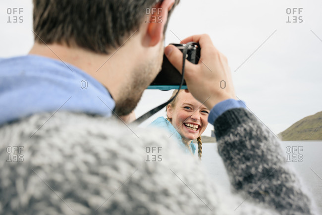Photographer taking picture of happy woman near sea