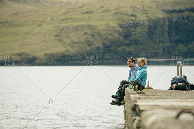 Man and woman sitting on concrete pier