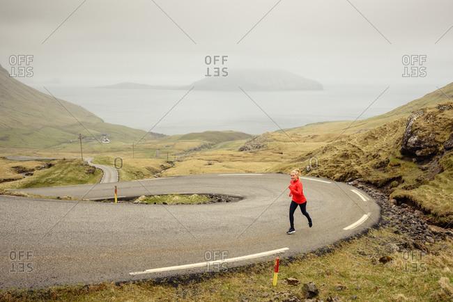 Sportswoman running on winding road
