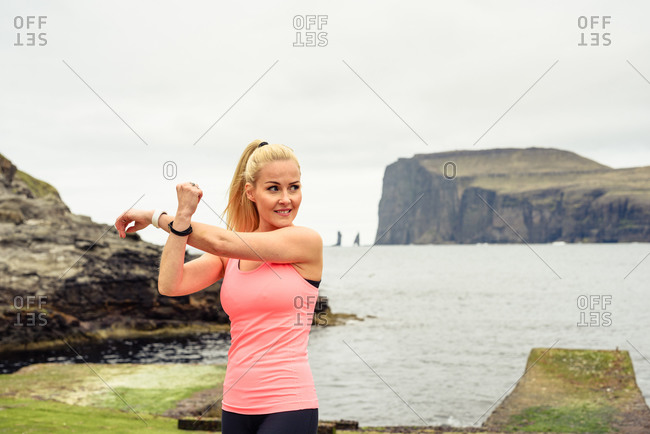 Adult sportswoman warming up on shore