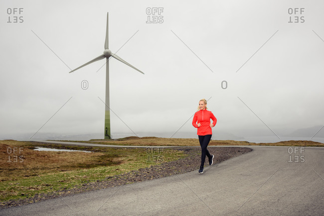 Female athlete running on countryside road