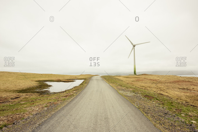 Road and windmill against gray sky