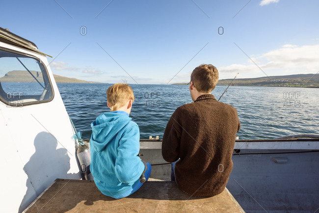 Man and boy on boat with fishing rod
