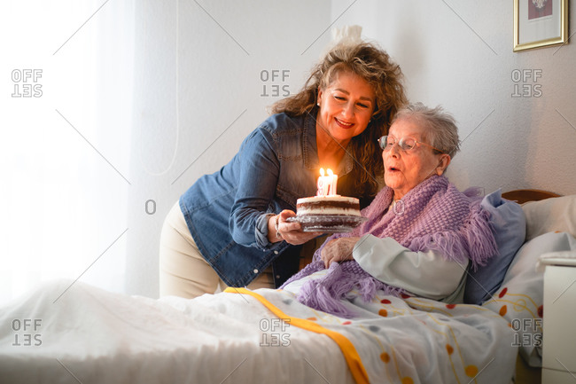 Old woman and daughter celebrates her 97th birthday with a cake