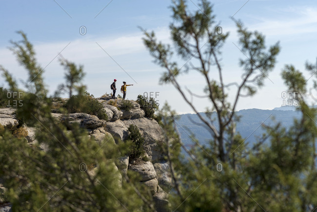 Two climbers standing on top of summit pointing with hand