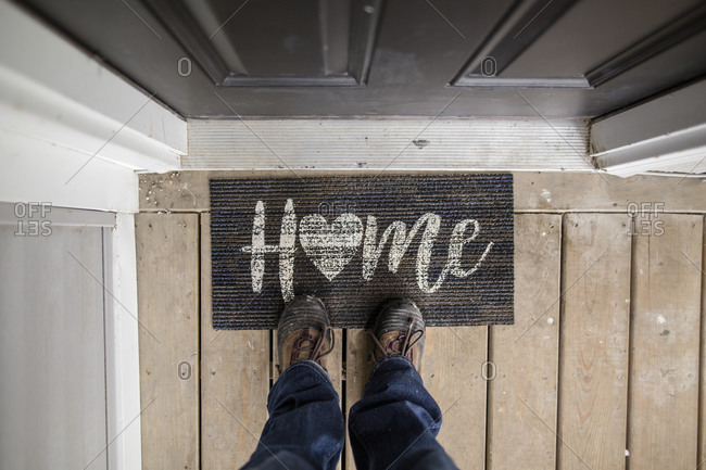 Close-up of person standing on doormat at the entry of a home