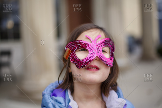 Close-up of small girl with bright eyes wearing a shiny butterfly mask