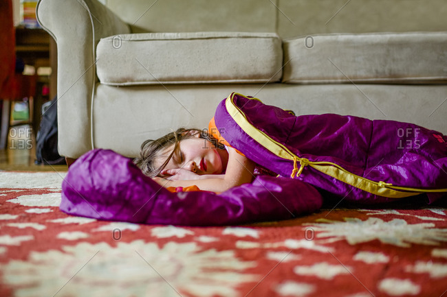 A beautiful little girl rests in a sleeping bag on the floor indoors
