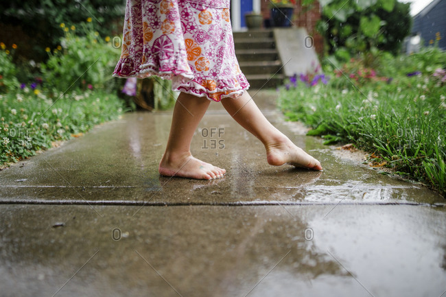 Close-up of a small barefoot child dancing on front stoop in the rain