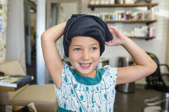 A happy little girl in a hair salon smiles with a towel on her head