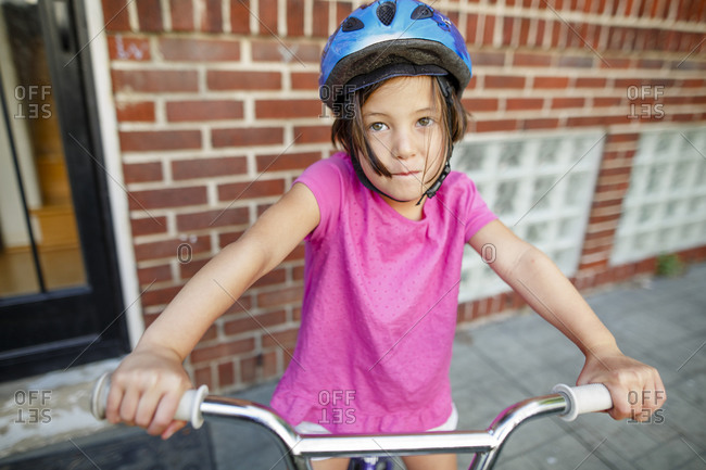 A cute little girl sits on her bike in front of house wearing a helmet