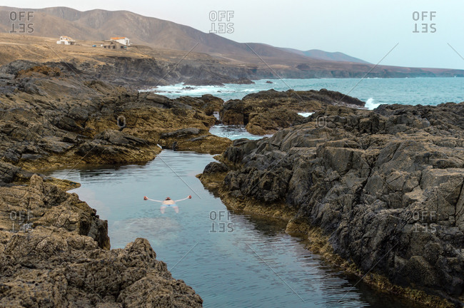 Man swimming and relaxing in natural sea pool on Fuerteventura island.