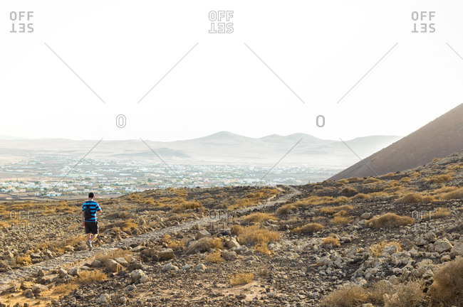 Man hiking through mountainous and desert landscape of Fuerteventura