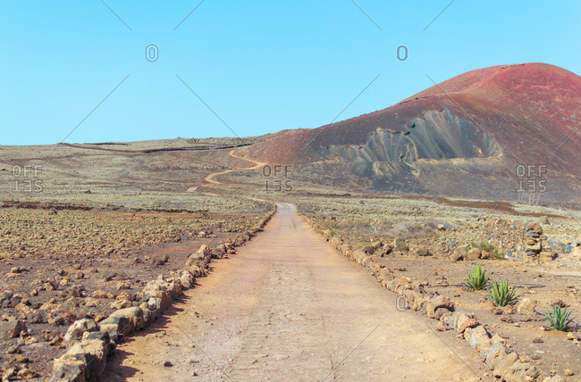 Desert and mountainous patch in arid landscape on sunny day.