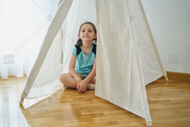 Girl looking inside a white teepee tent inside their house.