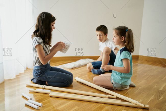 Children setting up a teepee tent inside their house.