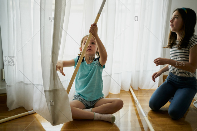 Girl putting the sticks to build a teepee tent inside their house.