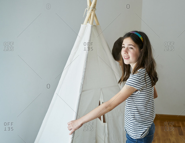 Children putting the sticks to build a teepee tent inside their house.