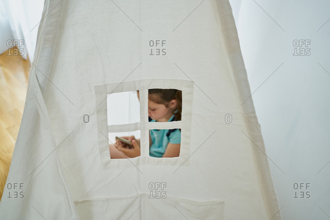Little girl looking at her smartphone inside a white teepee tent inside her house.