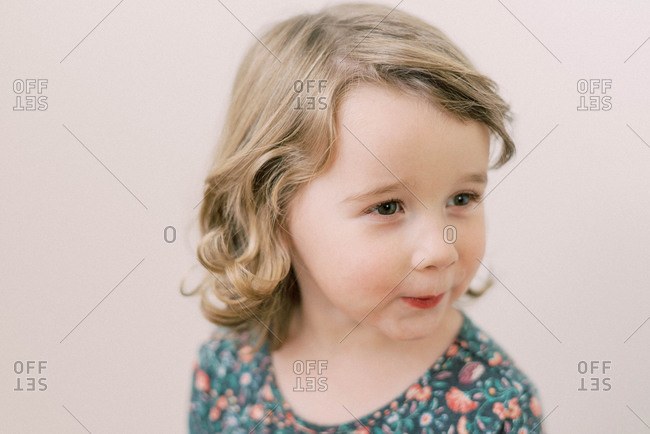 Little toddler girl with curly hair in front of neutral background