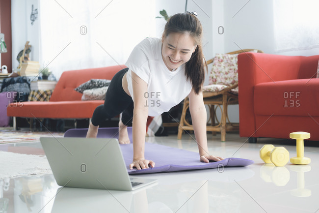 Fit woman doing yoga plank and watching online tutorials.