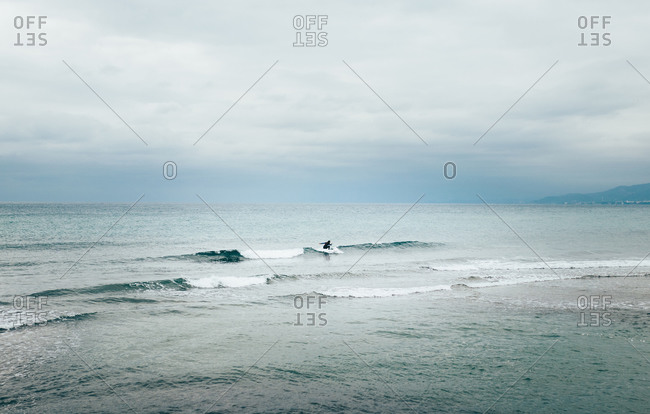 Silhouette in the center of a man surfing in the sea near the coast
