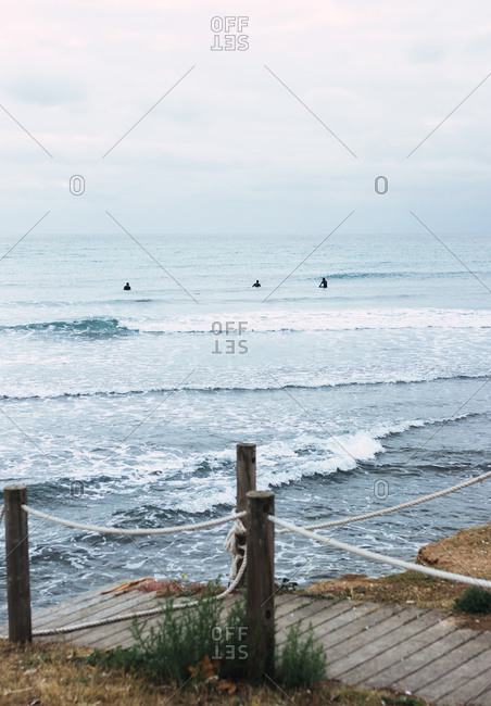 Silhouette of three male surfers resting on their boards in the sea